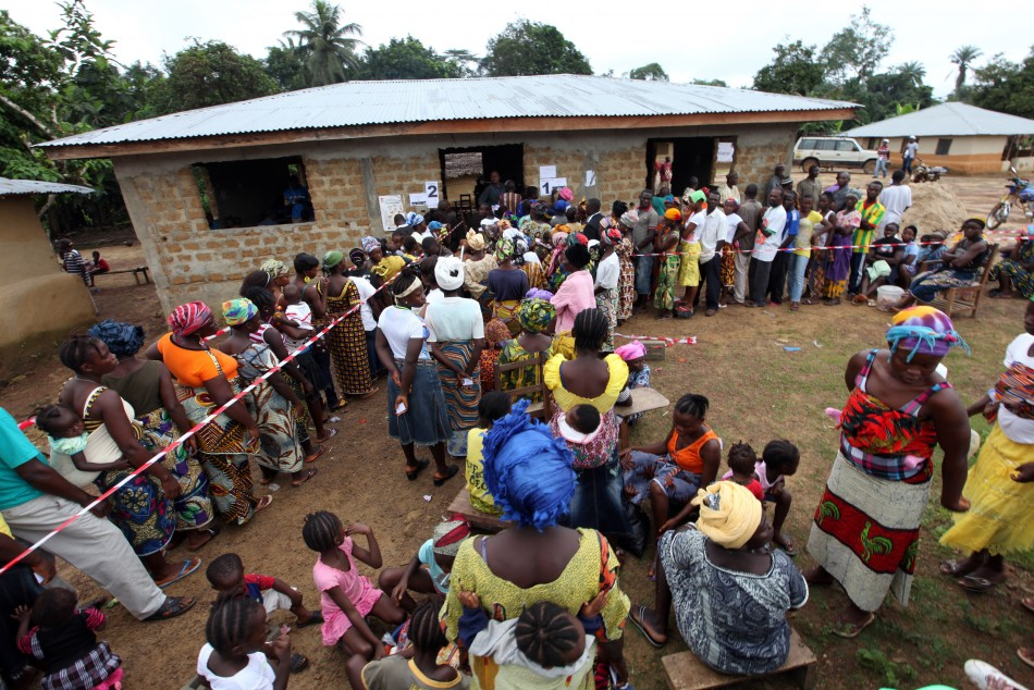 People wait to vote during a presidential election at a polling station in Feefee, Bomi county