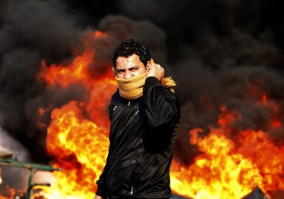 A protester stands in front of a burning barricade during the agitation in Cairo