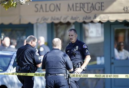 Police officers guard the entrance to Salon Meritage following a shooting that left six people dead and three injured in Seal Beach, California