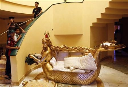 Libyans stand next to a golden sofa with a statue of Aisha