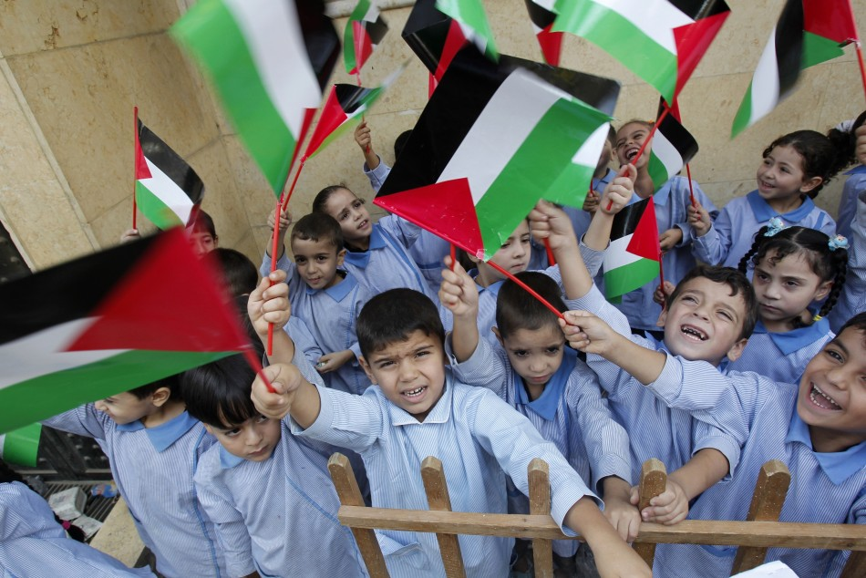 Palestinian children wave their national flags at the Palestinian Shatila refugee camp in Beirut