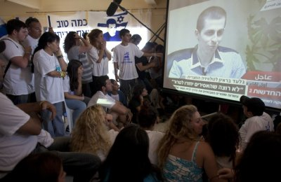 Israelis in Mitzpe Hila watch a television broadcast of an interview with Gilad Shalit
