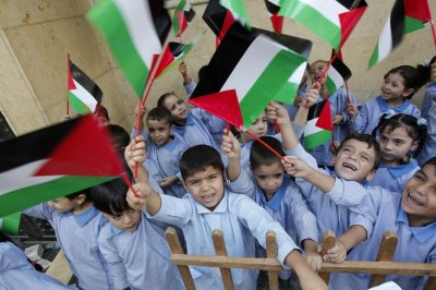 Palestinian children wave their national flags at the Burj al-Barajneh refugee camp in Beirut