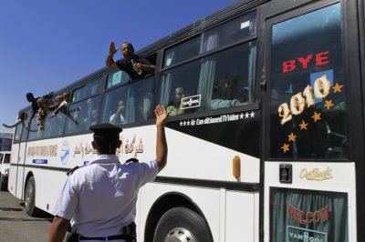 Released Palestinian prisoners wave from a bus as they make their way through the Rafah border crossing between Egypt and Gaza