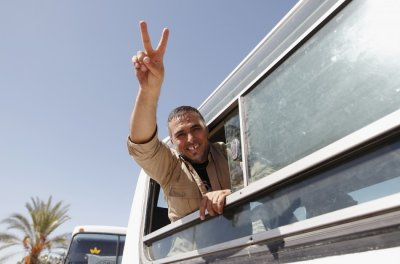 Palestinian prisoner, released by Israel in exchange for Israeli soldier Shalit, gestures from a bus as he makes his way through the Rafah border crossing between Egypt and Gaza