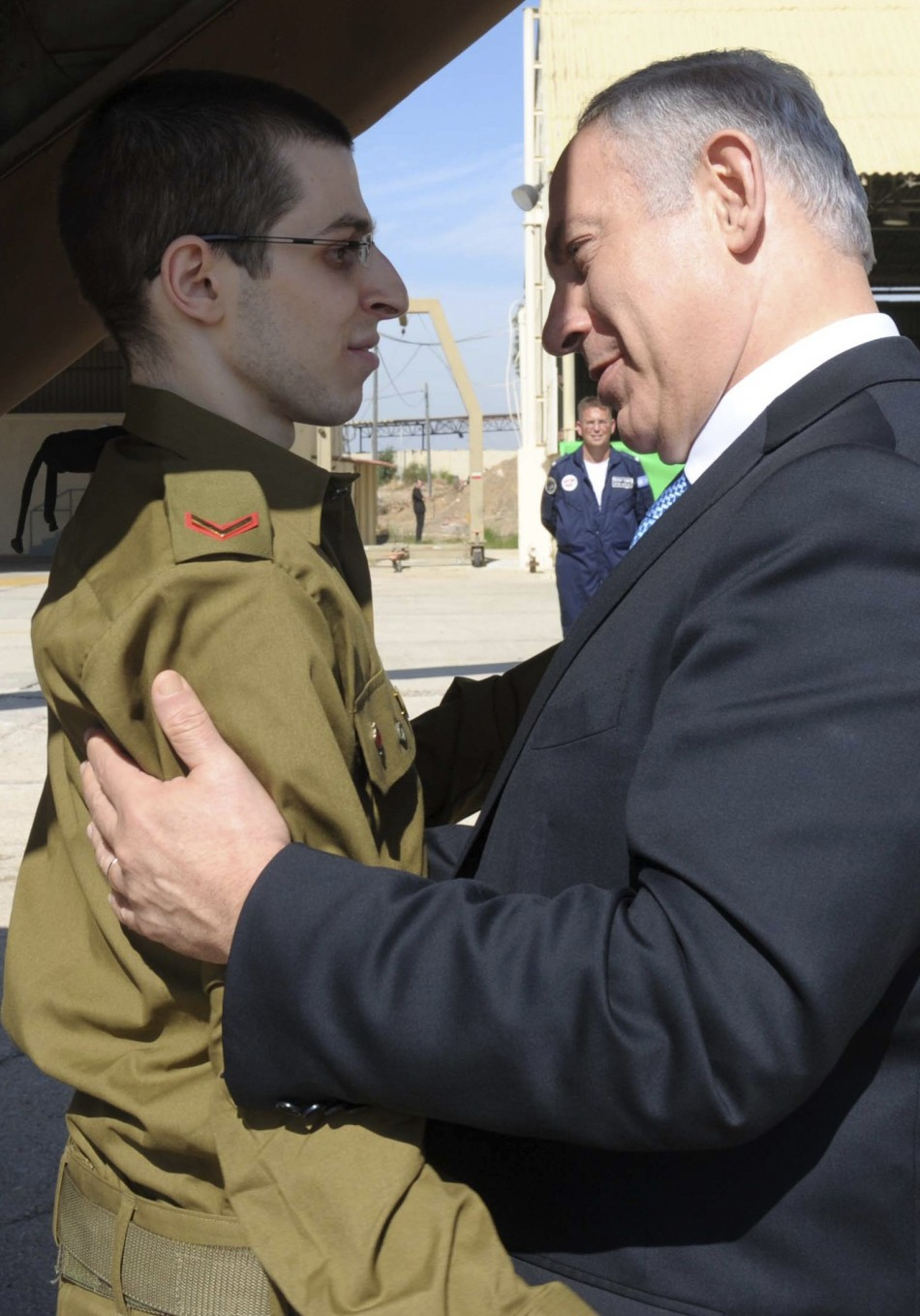 Israel's Prime Minister Benjamin Netanyahu (R) greets Israeli soldier Gilad Shalit at Tel Nof air base in central Israel in this handout picture released October 18