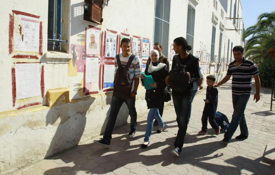 People walk past election posters in Tunis