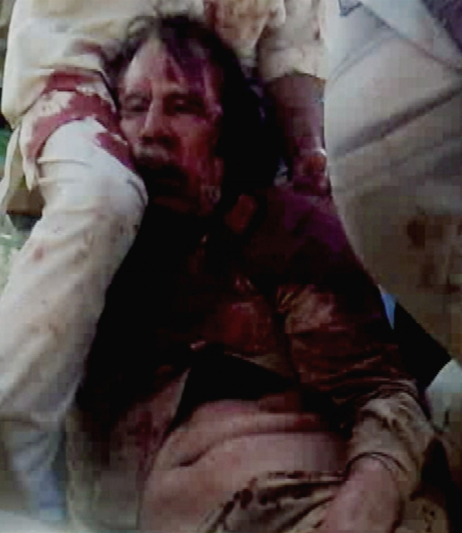 Frame grab of former Libyan leader Muammar Gaddafi, covered in blood, being held on the ground by NTC fighters in Sirte