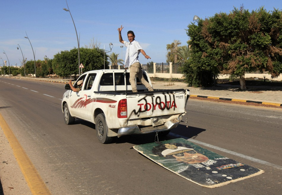 Anti-Gaddafi fighters gesture as they ride in a vehicle, trailed by an image of Muammar Gaddafi, after the fall of Sirte in the town