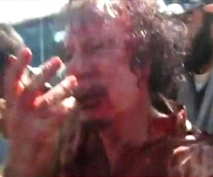 Frame grab of former Libyan leader Muammar Gaddafi, covered in blood, being pushed to the ground by NTC fighters in Sirt