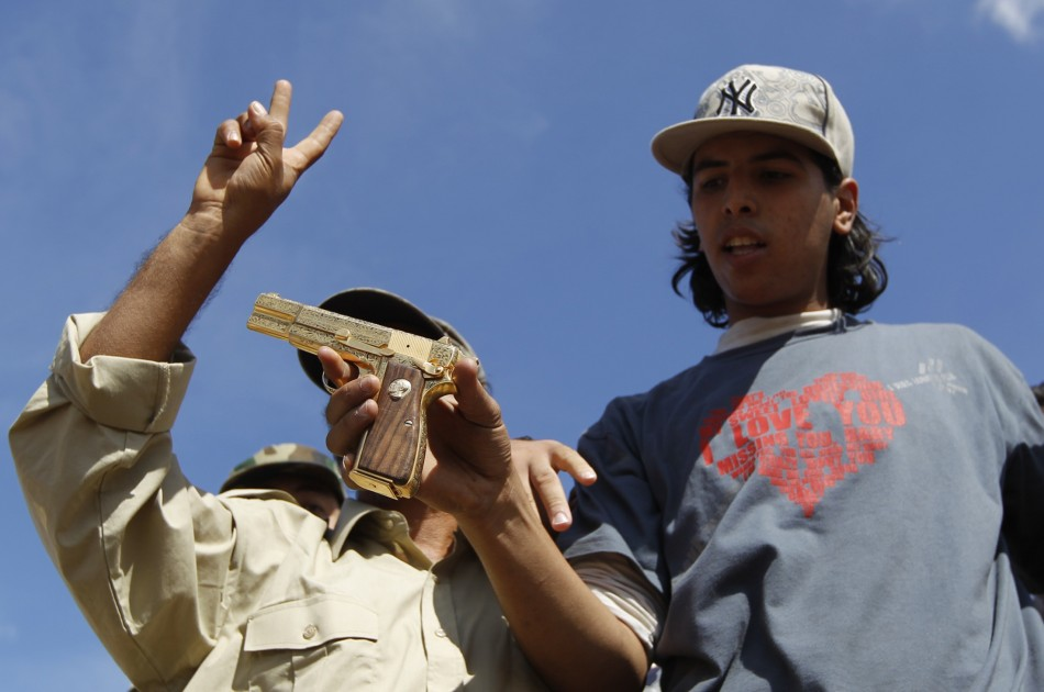 Anti-Gaddafi fighters show the media what they claim was the golden pistol of Muammar Gaddafi, near Sirte