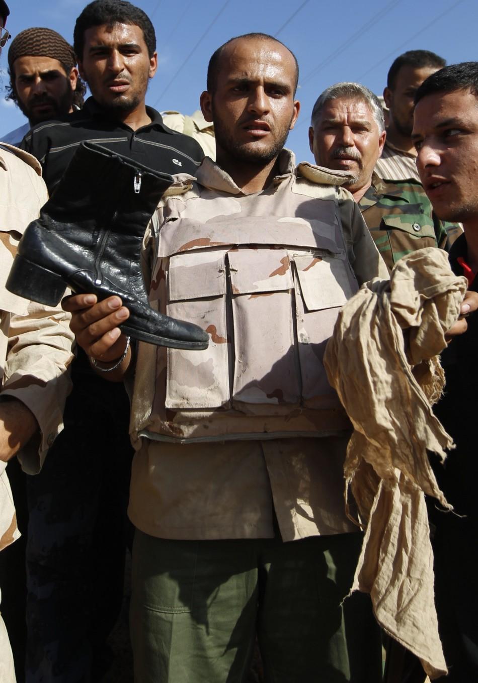 Anti-Gaddafi fighter shows the media clothes of Muammar Gaddafi near Sirte