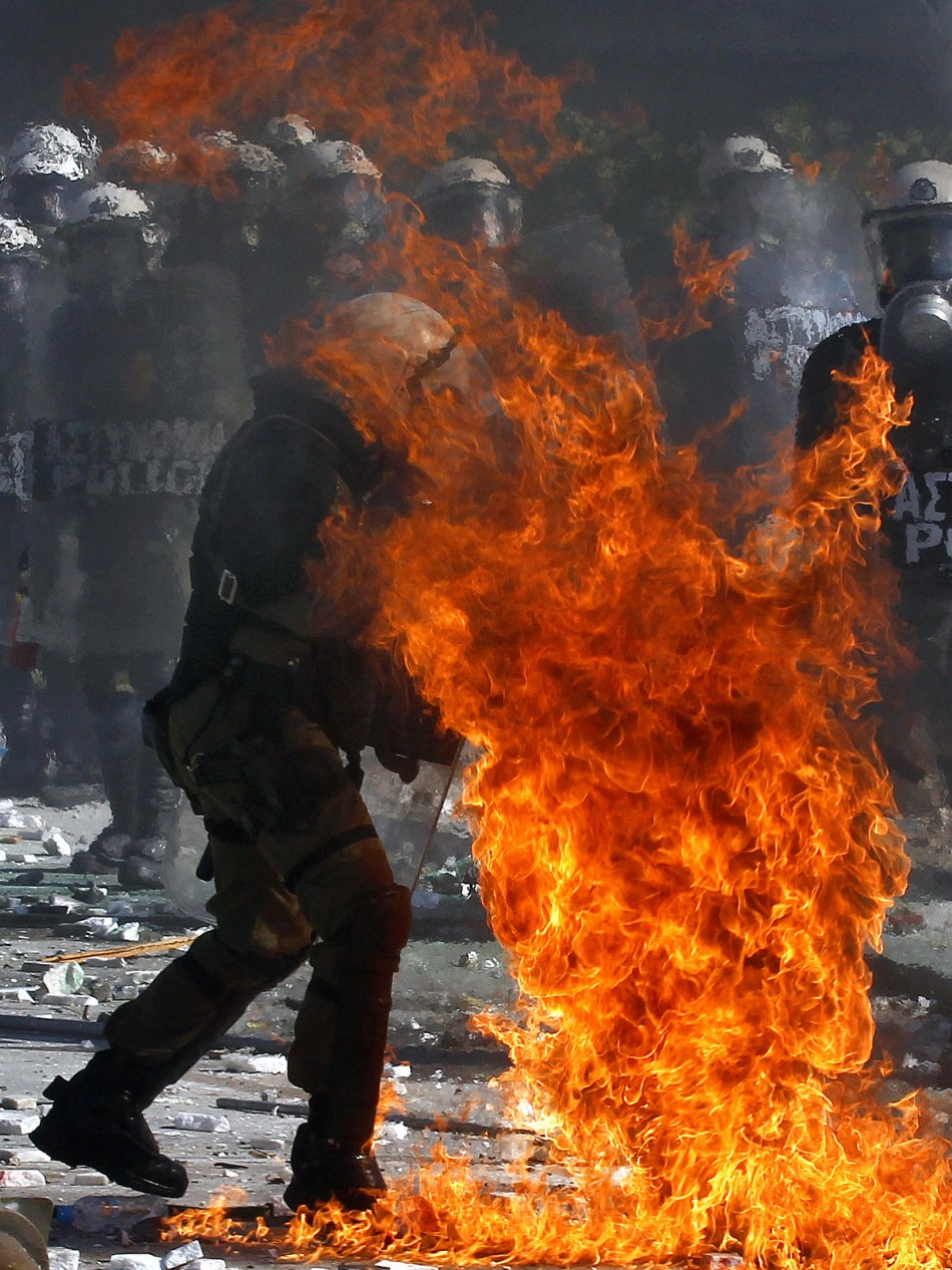 A Greek police officer is set partly on fire by an exploding petrol bomb, thrown by anti-austerity protesters, outside the parliament during clashes in Athens