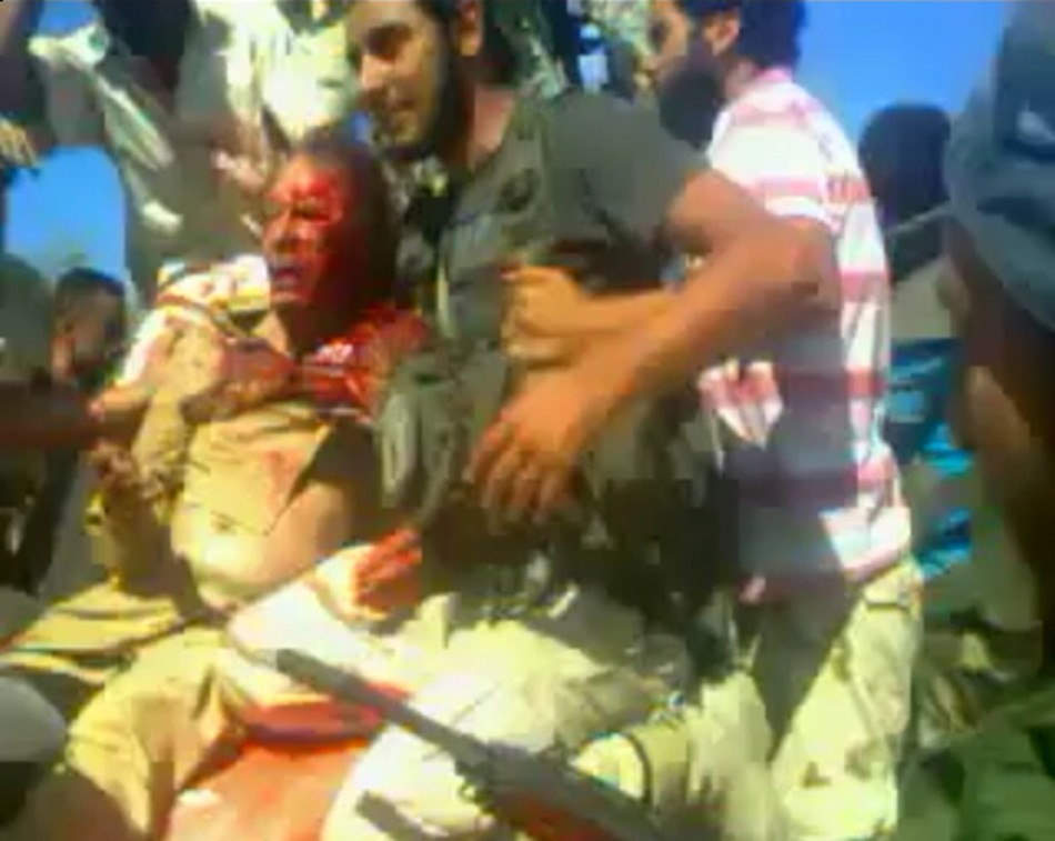 Frame grab shows former Libyan leader Muammar Gaddafi, covered in blood, after his capture by NTC fighters in Sirte
