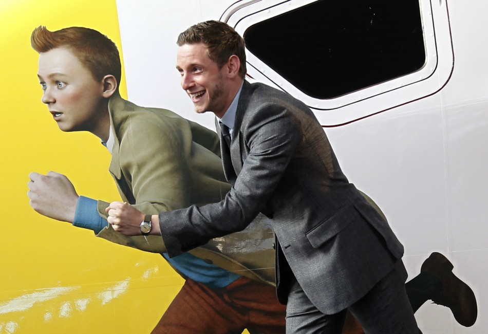 Actor Jamie Bell imitates a figure of Tintin, painted on a Thalys high-speed train, in Brussels