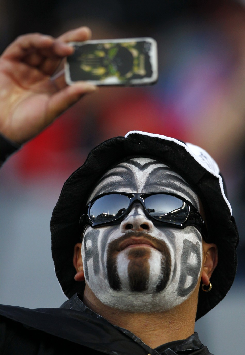 A New Zealand All Blacks039 fan takes a picture with his mobile phone before their Rugby World Cup final match against France at Eden Park in Auckland.
