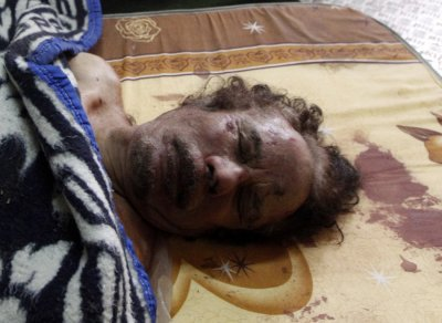 Dead body of Gaddafi is displayed inside a metal storage freezer in Misrata