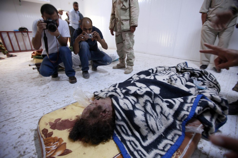 People take pictures of the body of former Libyan leader Muammar Gaddafi inside a meat locker in Misrata