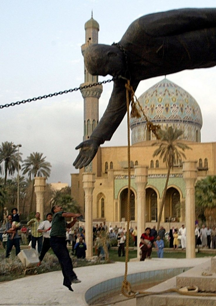 An Iraqi man throws stones at a statue of Iraq's President Saddam Hussein as it falls in central Baghdad April 9, 2003. U.S. troops pulled down a 20-foot (six metre) high statue of President Saddam Hussein in central Baghdad on Wednesday and Iraqis d