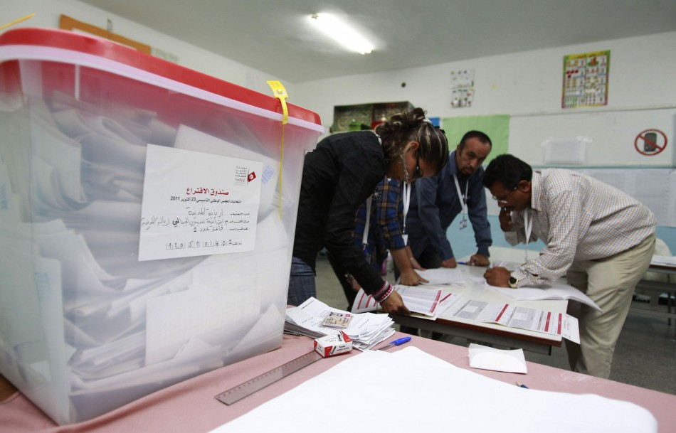 Officials collect votes from ballot boxes after the polls closed in a polling station in Tunis