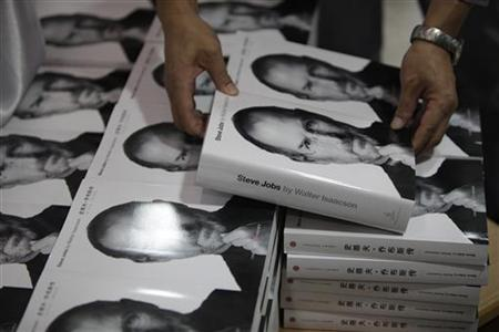 "Man holds copy of authorized biography titled ""Steve Jobs"" near copies of the book officially translated into Chinese at a bookstore in Shanghai"