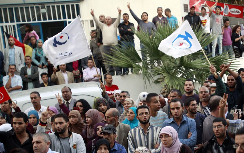 Supporters of the Islamist Ennahda movement hold party flags during Abdelhamid Jlazzi's speech outside the party's headquarters in Tunis