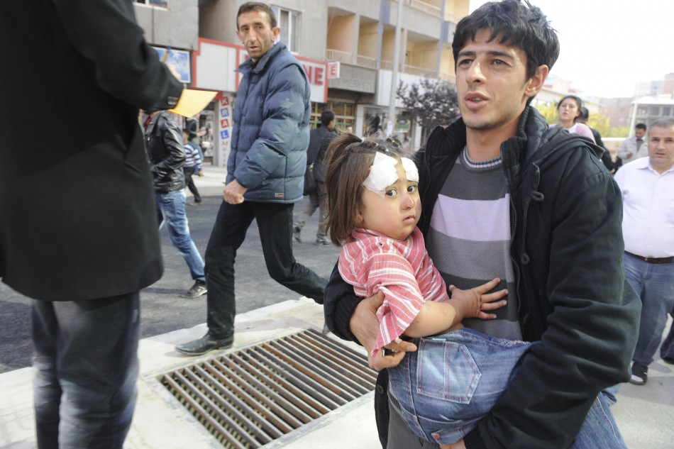 A man carries an injured girl after an earthquake in Tabanli village near the eastern Turkish city of Van on Monday.