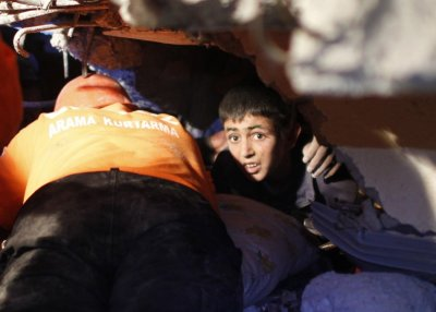Yunus, a 13-year-old earthquake survivor, waits for to be rescued from under a collapsed building by rescue workers in Ercis, near the eastern Turkish city of Van on Monday.