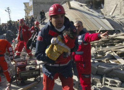 A rescue worker carrying a girl runs to an ambulance after his team found her alive in a collapsed building in Ercis, near the eastern Turkish city of Van on Monday.