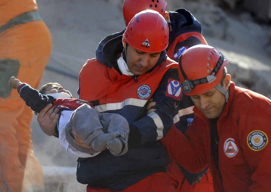 A rescue worker carries a boy to an ambulance after his team found him alive in a collapsed building in Ercis on Monday.