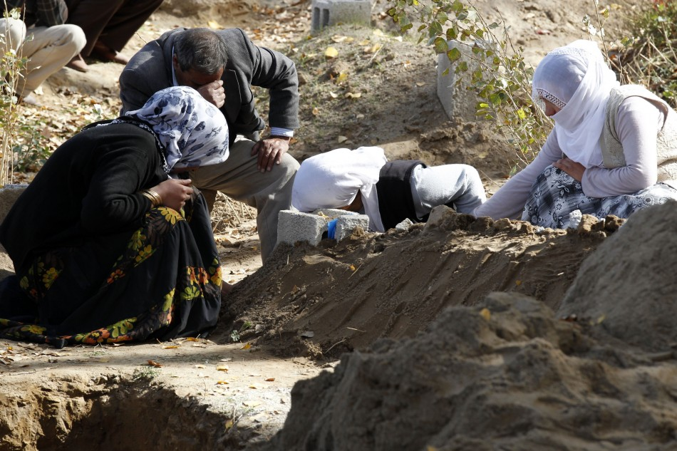 Survivors mourn over the grave of one of their relatives, killed during the earthquake, in Ercis on Monday.