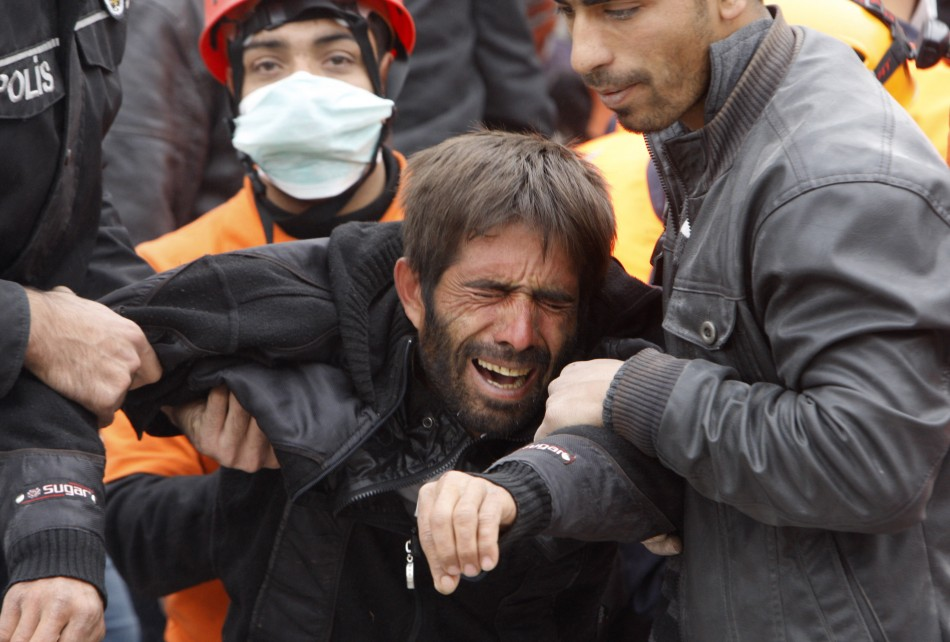 A man reacts as rescue workers carry out an earthquake victim from a collapsed building in Ercis, near the eastern Turkish city of Van on Tuesday.