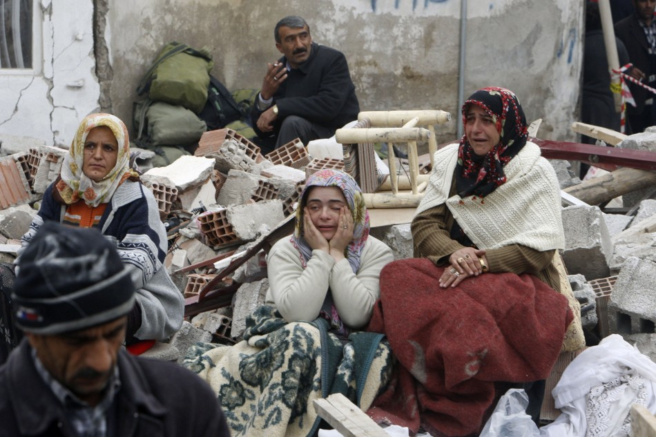 Earthquake survivors sit on the debris of a collapsed building in Ercis on Tuesday.