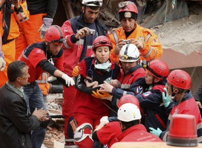 Rescue workers carry a 14-day-old newborn baby, which was rescued alive 46 hours after the earthquake, from the rubble of a collapsed building  in Ercis on Tuesday.
