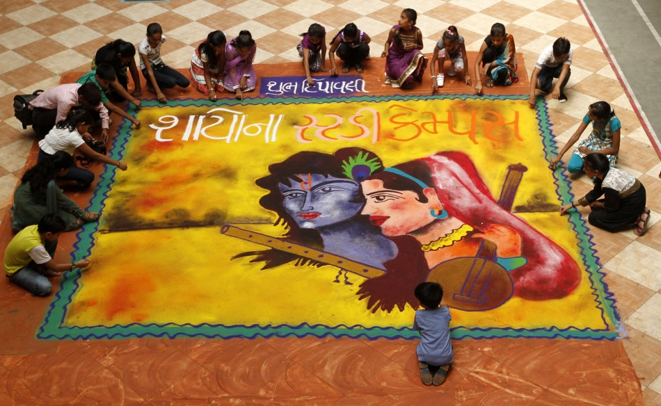 Students put finishing touches to a quotrangoliquot, or mural made out of coloured powders, at a school ahead of Diwali festival celebrations in Ahmedabad on October 21, 2011.