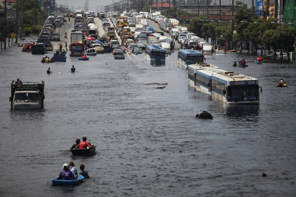 Vehicles are parked on an elevated highway to avoid floodwater in the north of Bangkok