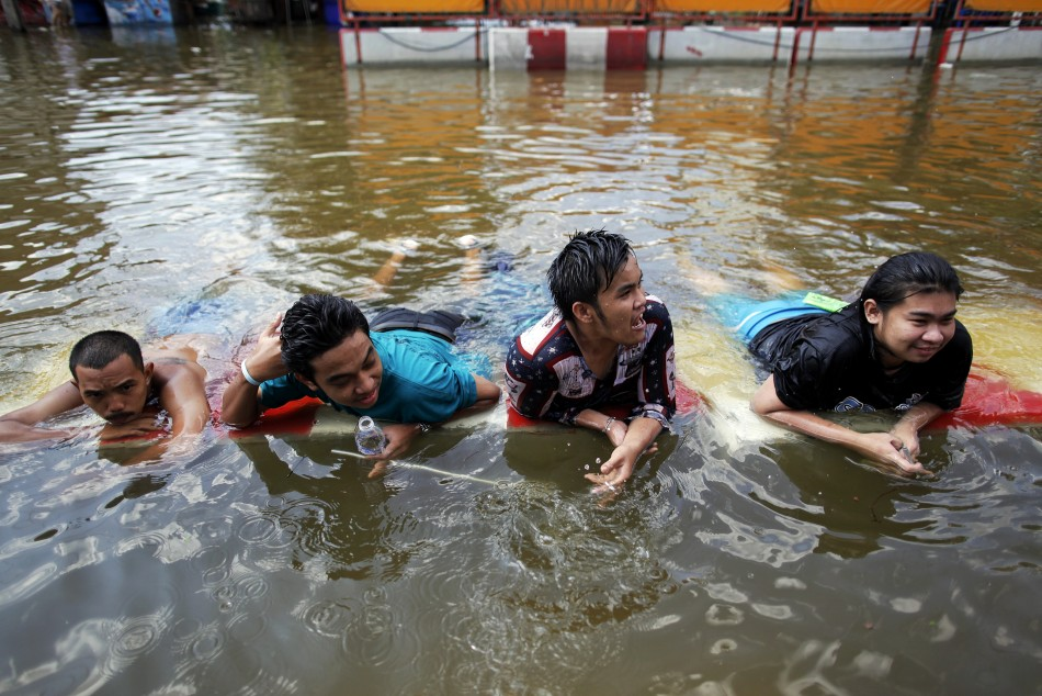 People take a break in water after floods advanced into their neighborhood near Chao Praya river in central Bangkok