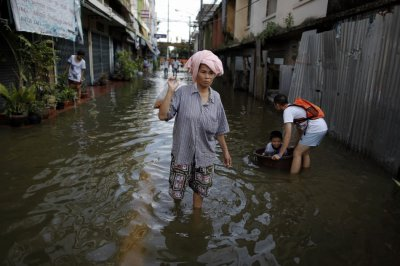 A woman carries food after floods advanced into her neighborhood near Chao Praya river in central Bangkok