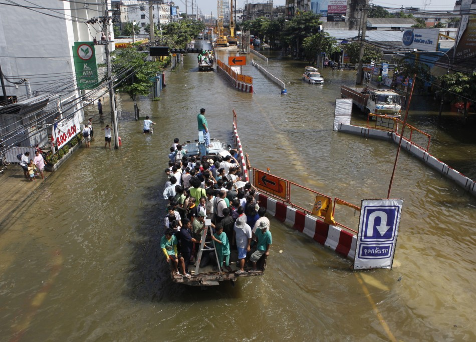 eople are transported on a truck through the flooded streets at Bang Phlat district in Bangkok