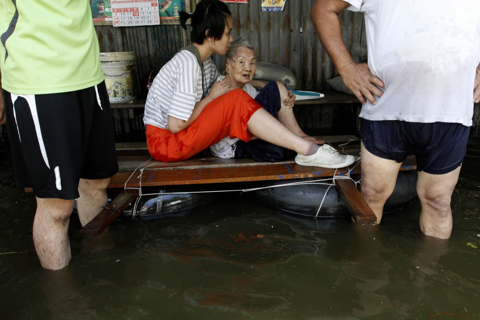 An elderly woman is evacuated as the floods advance into Bangkok