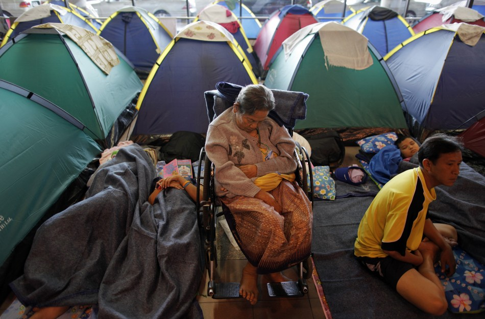 People evacuated from areas affected by floods pass time at a collective shelter at Don Mueang airport in Bangkok