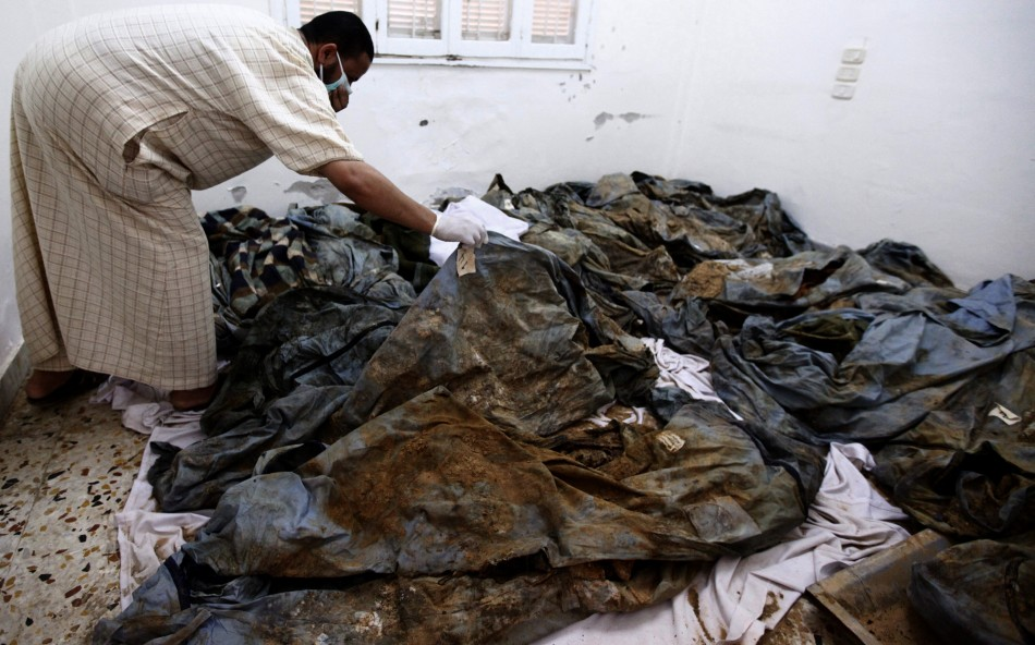 A man tries to identify his lost relatives among unearthed bodies suspected to have been killed by Gaddafi's forces in Khums