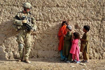 Corporal Calum Cooper Argyll and Sutherland Highlanders, 5th Battalion The Royal Regiment of Scotland, talks to local children while he carries out searches on compounds in Afghanistan. This picture, taken by Sgt Rupert Frere, won the Best Overall Image.