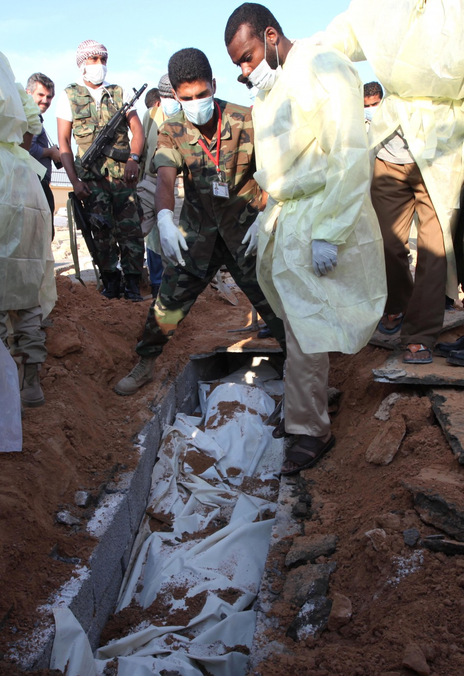 Medical and militia officials in Tripoli exhume two corpses from a site they identified as a mass grave