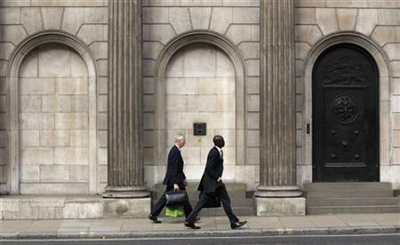 Two men walk past the Bank of England in the City of London