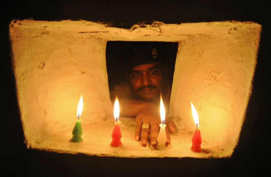 An Indian BSF soldier lights a candle inside a bunker on the occasion of the Hindu festival of Diwali at the India-Bangladesh border on the outskirts of Agartala