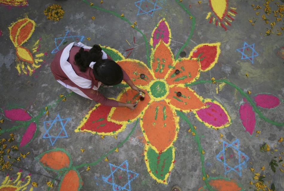 Students put the finishing touches to a rangoli, or a mural