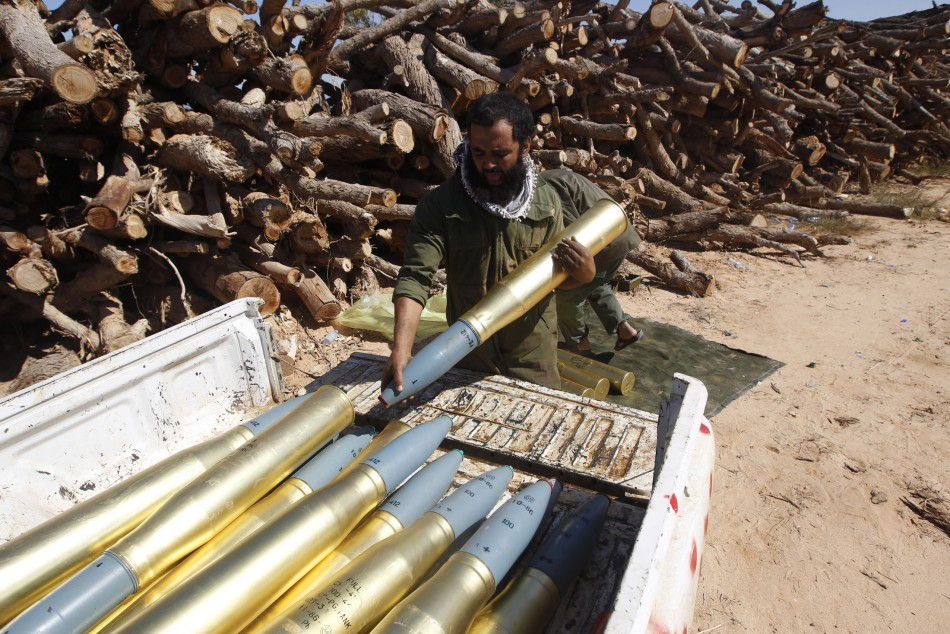 An anti-Gaddafi fighters loads tank shell on a pickup truck during a clashes with pro-Gaddafi forces in Sirte
