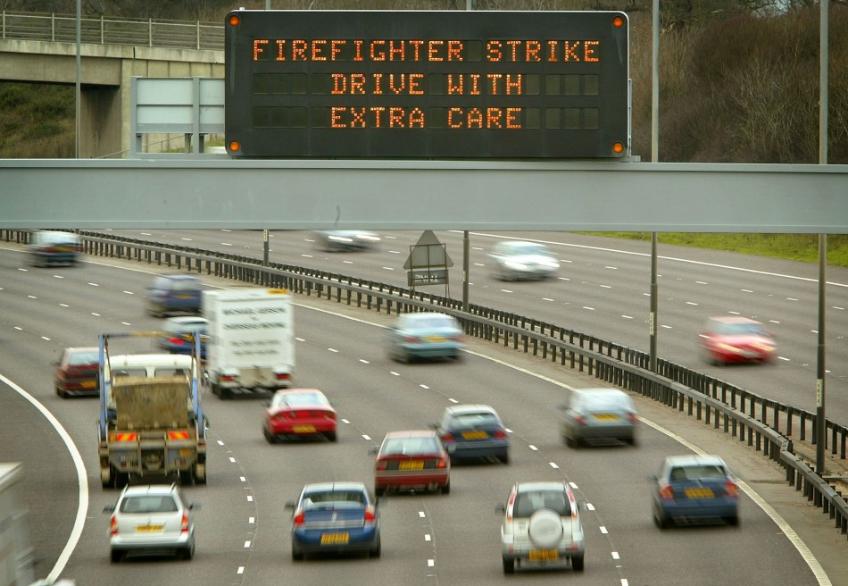 A SIGN ENCOURAGING MOTORISTS TO DRIVE WITH CARE OVERLOOKS THE M25 MOTORWAY IN BUCKINGHAMSHIRE.