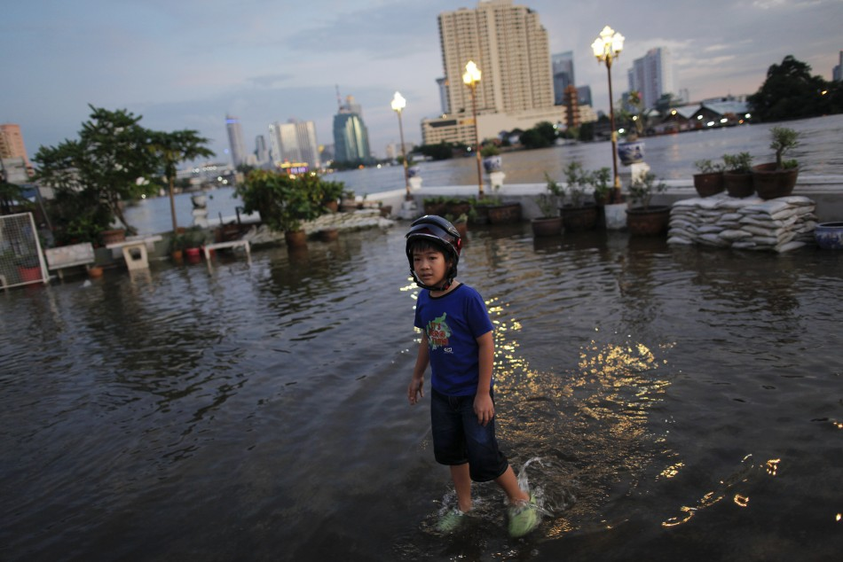 Korn walks through a flooded neighborhood near Chao Phraya river in central Bangkok